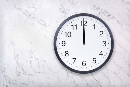 Wall clock show the twelve oclock on white marble texture. Office clock show midday or midnight on marble background