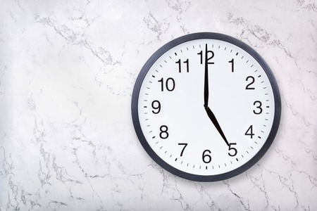 Wall clock show five oclock on white marble texture. Office clock show 5pm or 5am on marble background
