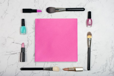 Flat lay of cosmetic products with blank pink paper card on white marble background. Makeup mockup. Lipstick, brushes and nail polish on marble texure