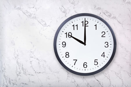 Wall clock show ten oclock on white marble texture. Office clock show 10pm or 10am on marble background