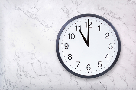 Wall clock show eleven oclock on white marble texture. Office clock show 11pm or 11am on marble background