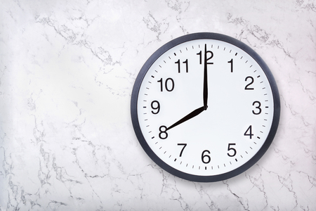 Wall clock show eight oclock on white marble texture. Office clock show 8pm or 8am on marble background