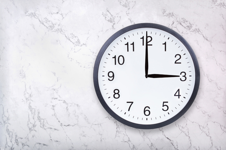 Wall clock show three oclock on white marble texture. Office clock show 3pm or 3am on marble background
