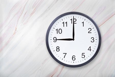 Horloge murale montre neuf heures sur la texture du marbre. L'horloge de bureau montre 21h ou 9h sur une texture de marbre avec un motif naturel