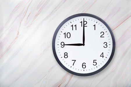 Wall clock show nine oclock on marble texture. Office clock show 9pm or 9am on marble texture with natural pattern