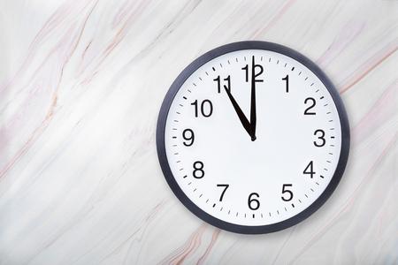Wanduhr zeigt elf Uhr auf Marmorbeschaffenheit. Bürouhr zeigen 23 Uhr oder 11 Uhr auf Marmorstruktur mit natürlichem Muster Standard-Bild