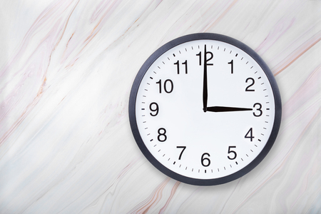 Wall clock show three oclock on marble texture. Office clock show 3pm or 3am on marble texture with natural pattern