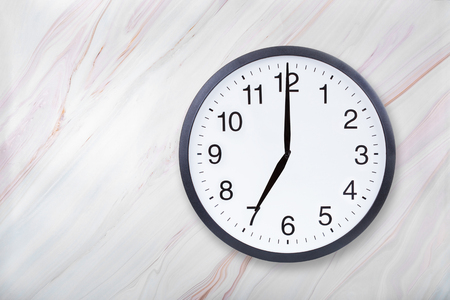 Wall clock show seven oclock on marble texture. Office clock show 7pm or 7am on marble texture with natural pattern Stock Photo
