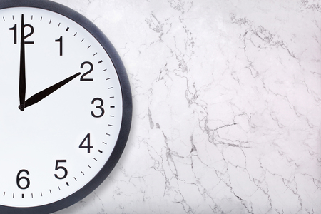 Closeup of wall clock show two oclock on white marble texture. Office clock show 2pm or 2am on marble background. Crop image Фото со стока