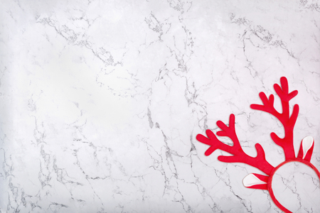 Red antlers of a deer headband on marble background. Pair of toy reindeer horns on white marble texture