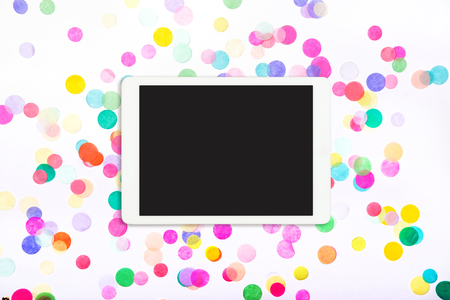 Touchpad with blank screen on colorful confetti background. Tablet computer on white background with confetti. Flat lay. Top view