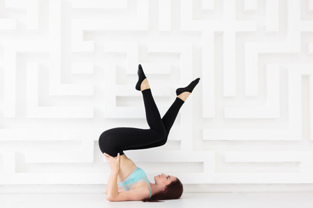 Young beautiful woman working out in studio while practicing pose with lifted legs. Side view