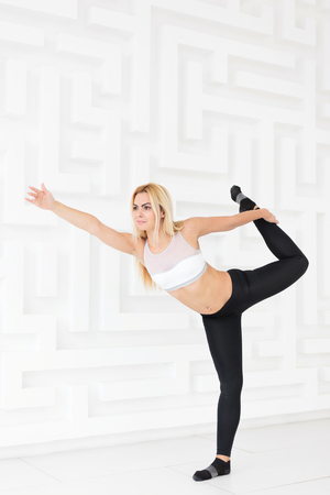 Young sporty woman practicing stretching and balance exercise while standing in Dancer pose. White studio wall background 写真素材 - 120777210