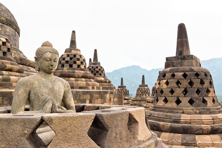 Buddah statue with ancient stupas in Borobudur Buddhist temple. Mahayana Buddhist temple in Java