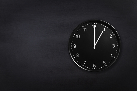 Black wall clock showing one oclock on black chalkboard background. Office clock showing 1am or 1pm on black texture