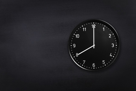 Black wall clock showing eight oclock on black chalkboard background. Office clock showing 8am or 8pm on black texture