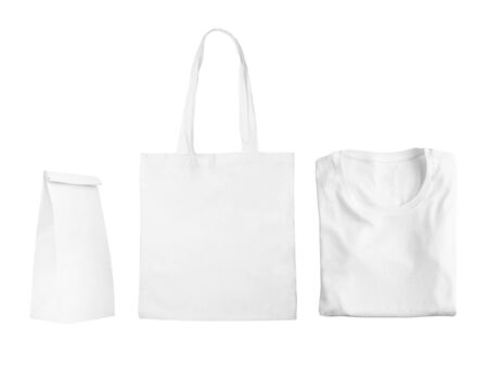 Collection of white objects isolated on white background. White cotton bag, white folded t-shirt, paper bag package. Flat lay of branding or identity mockup design. Imagens