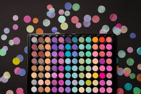 Eyeshadow palette on a black background with scattered confetti. Top view. Flat lay