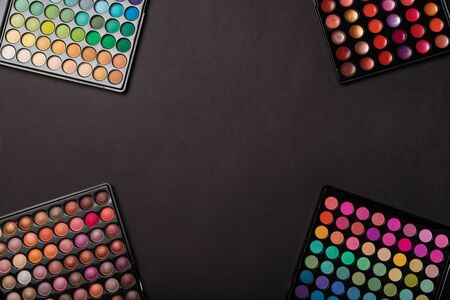 Colorful eyeshadow palettes on black background with a place for your copy space. Flat lay. Top view