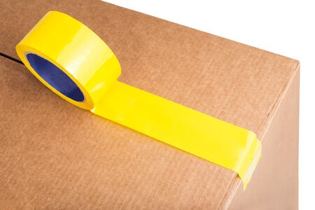 Closeup of cardboard box with yellow adhesive tape