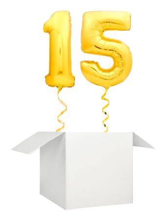 Golden number fifteen inflatable balloon with golden ribbon flying out of blank white box isolated on white background Stock Photo