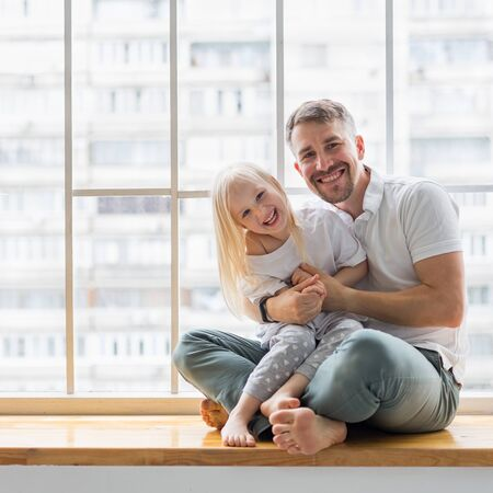 Young man holding her 3,5 years old daughter while sitting on window sill. Happy dad hugs her little girl while sitting together