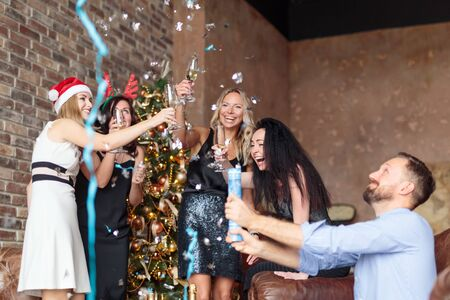 Young happy people having fun at Ney Years party with confetti and champagne in modern loft decorated with Christmas tree