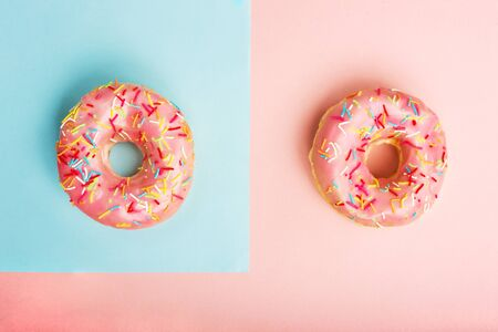 Two donuts decorated with sprinkles on pink and blue paper background. Coral and blue donut background. Flat lay