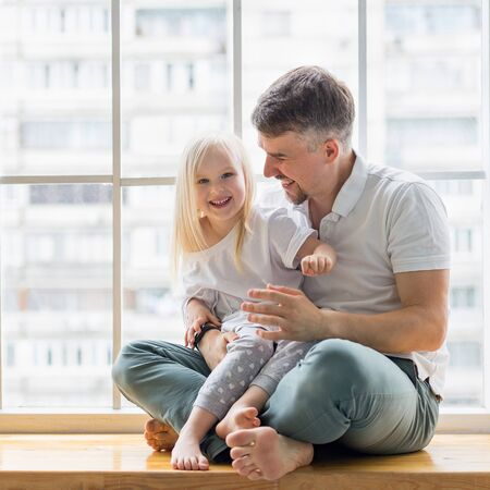 Handsome father sitting on windowsill while hugging his daughter. Young father having fun with his cute daughter while sitting in front of window