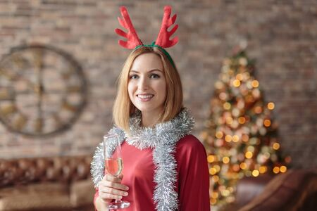 Happy young woman wearing red dress and funny headband drinking champagne in modern loft. Decorated Chistmas tree and clock on a background 스톡 콘텐츠