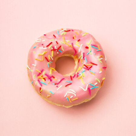 Pink donut decorated with sprinkles on coral background. Flat lay. Top view Foto de archivo