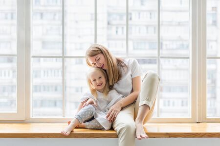 Young mother holding her 3,5 years old daughter while sitting on window sill. Happy mom hugs her little girl while sitting together