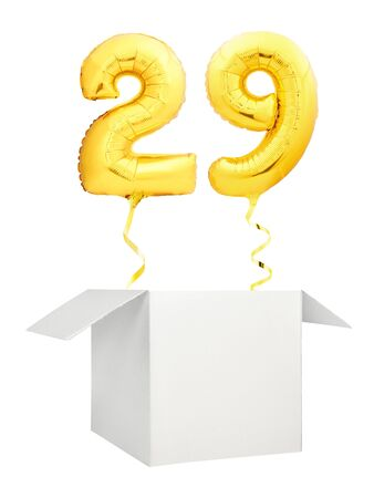 Golden number twenty nine inflatable balloon with golden ribbon flying out of blank white box isolated on white background Foto de archivo