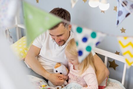 Happy father reading book with his 3 years old girl while sitting on decorated bed together. Young father reading a book while hugging his cute daughter 版權商用圖片