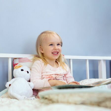 Happy 3 years old cute girl reading a book while sitting and smiling in bed before bedtime