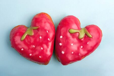 Sweet heart-shaped strawberry cakes on blue background. Sweet cakes for Valentines day. Flat lay. Top view