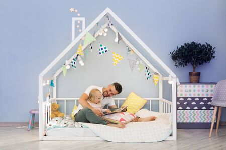 Happy father dad in cute house bed with blonde daughter reading stories at bedtime. Closeness relationships. Fatherhood concept