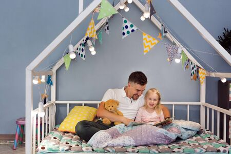 Father dad in bed with daughter reading stories at bedtime. Closeness relationship and love Stock Photo