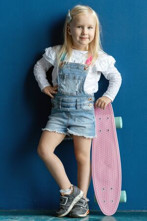 Portrait of happy smiling toddler girl with blond hair holding a pink skateboard while posing on blue wall background