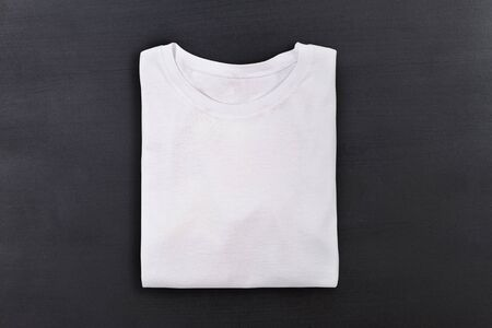 White folded t-shirt on black chalkboard background. Flat lay. Top view Archivio Fotografico