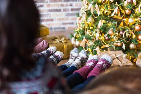 Young women wearing Christmas socks sitting near decorated Christmas tree. Rear view Stock Photo