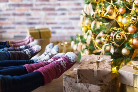 Close-up of young people dressed in Christmas socks sitting near decorated Christmas tree with gift boxes