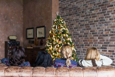 Young women chatting while sitting on the sofa near decorated Christmas tree in the loft. Rear view Archivio Fotografico