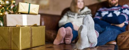 Young couple wearing warm socks sitting on the sofa near Christmas gift boxes. Cropped image