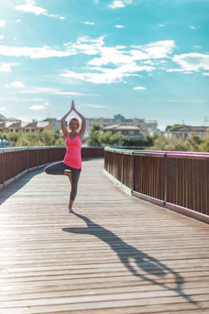 Young woman practicing yoga with hands raised up outdoors on a wooden bridge against blue sky with clouds. Long shadow on the wooden floor. Upward Salute pose or Urdhva Hastasana asana.