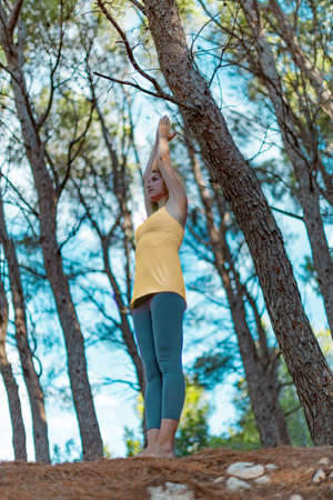 Young woman wearing sportswear practicing yoga with hands raised up in a forest outdoors. Upward Salute pose or Urdhva Hastasana asana.