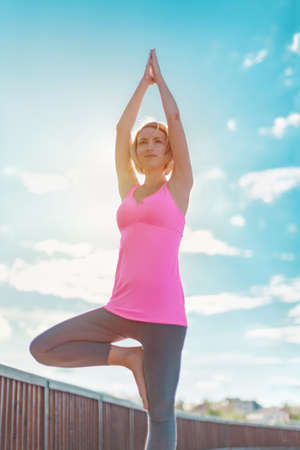 Young happy blonde woman practicing yoga with hands raised up outdoors against blue sky with clouds. Close-up of Upward Salute pose or Urdhva Hastasana asana.
