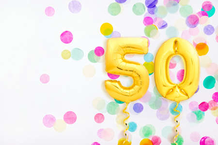 Number 50 fifty made of golden inflatable balloons with golden ribbons on colorful confetti background. Birthday party or anniversary concept