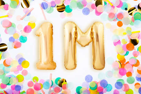 One million followers concept made of golden inflatable balloons in the frame of colorful confetti on white background. Top view. Flat lay