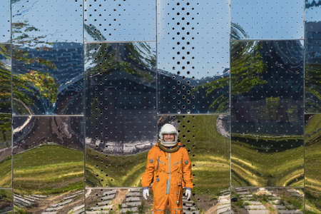 Astronaut wearing orange spacesuit and space helmet near the mirror wall with reflections